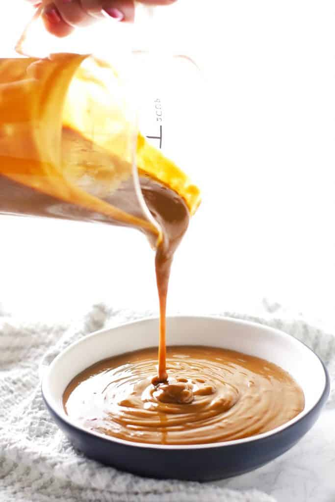 Peanut sauce being poured into bowl.