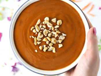 Hand holding bowl of spicy peanut sauce.