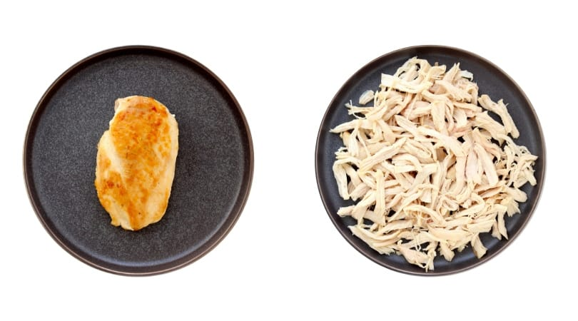Chicken breast on plate next to plate of shredded chicken.