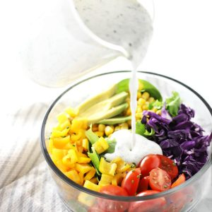 Healthy ranch dressing being poured on salad.