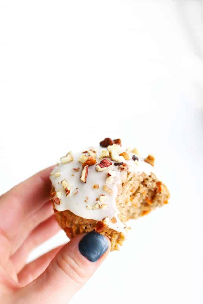 Healthy carrot cake muffin with a bite taken out of it.