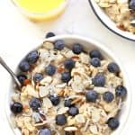 Blueberry oatmeal in bowl with glass of orange juice.