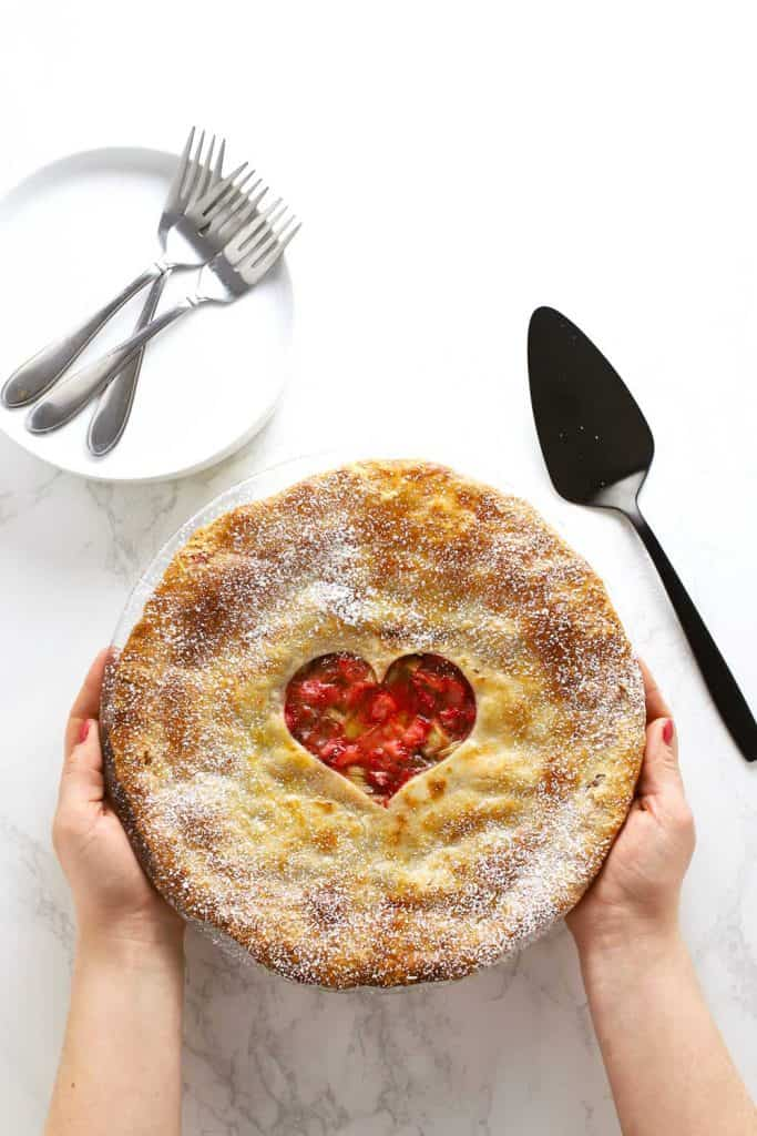 Two hands holding a strawberry rhubarb pie.