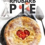 Pie with heart shaped crust on a grey napkin.