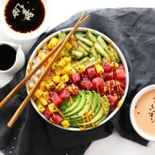 Tuna poke sushi bowl on grey napkin with chopsticks.