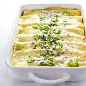 Vegetarian black bean enchiladas in a white dish.