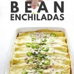 Enchiladas in white casserole dish topped with herbs, jalapeños and onions.