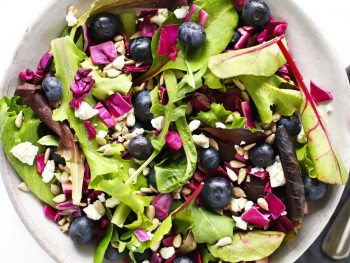 Blueberry goat cheese salad in grey bowl with fork and blue napkin.