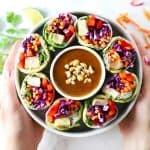Two hands holding white bowl with summer rolls and peanut sauce.