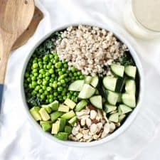Green grain summer salad in white bowl with wood serving utensils.