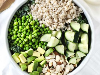 Green grain summer salad in white bowl.