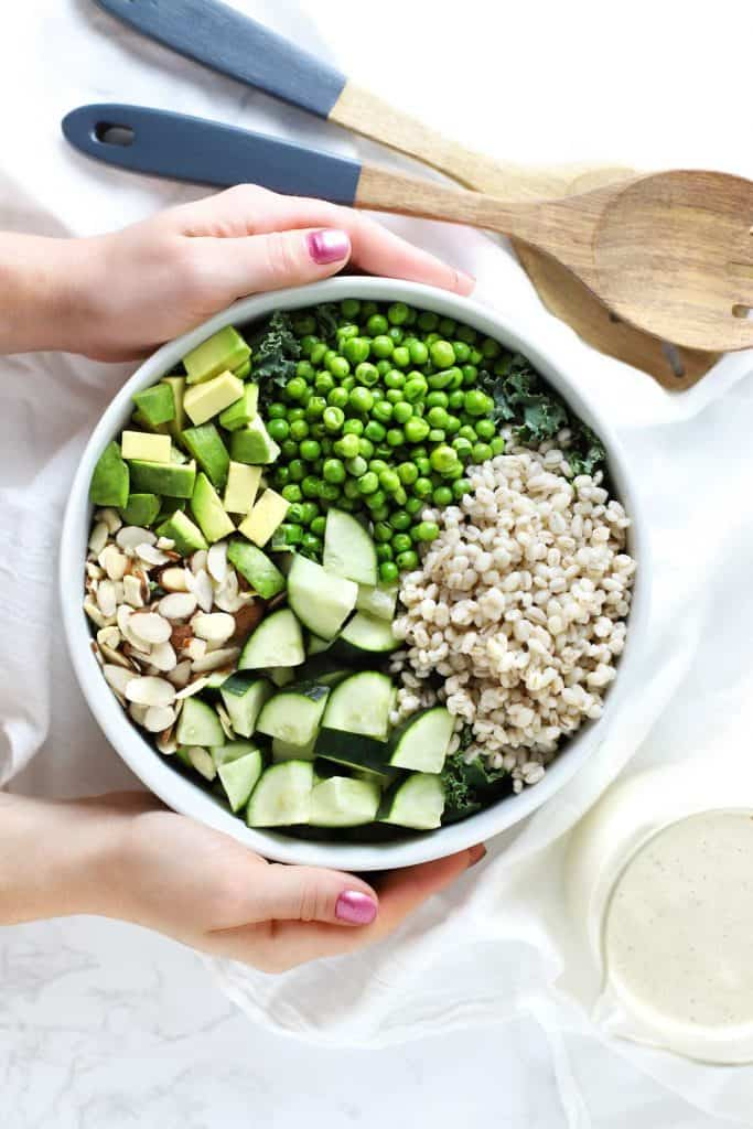 Two hands holding green grain summer salad in white bowl.