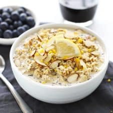 Lemon poppy seed overnight oats in a white bowl with blueberries and coffee.
