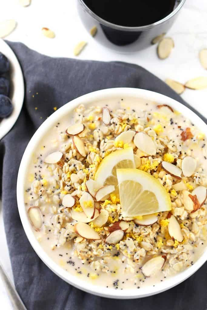 Lemon poppy seed overnight oats in a white bowl with lemon wedges and grey napkin.