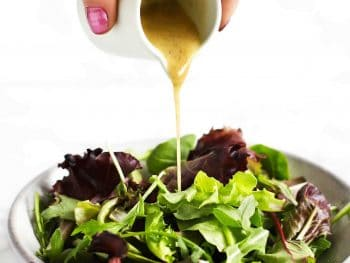 Roasted garlic vinaigrette being poured on salad.