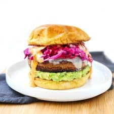 Black bean veggie burger on white plate with blue napkin.