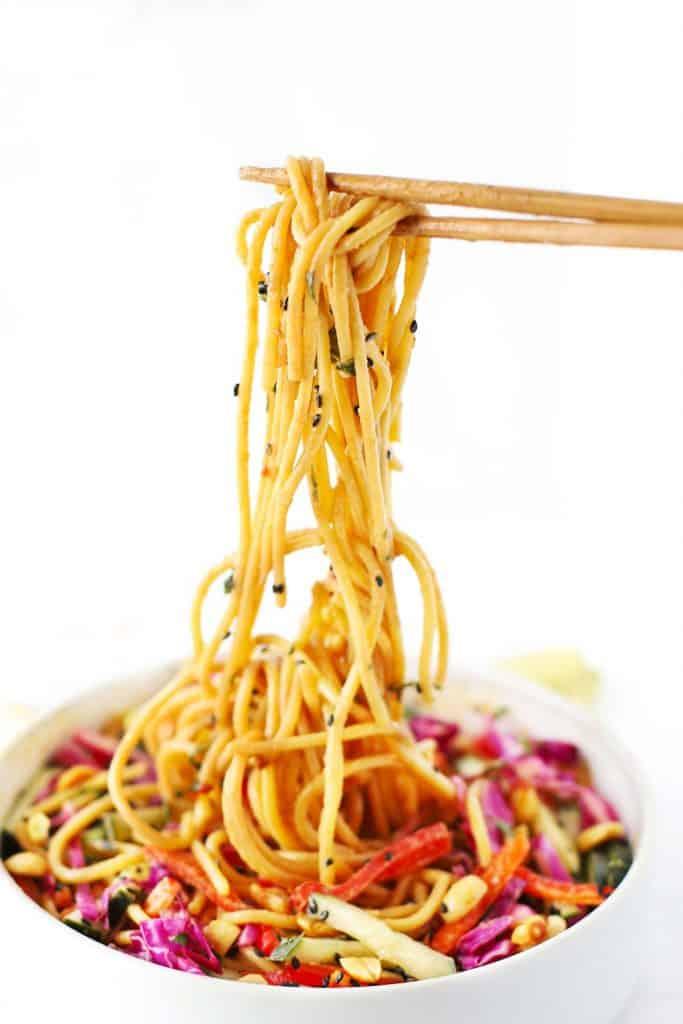 Chopsticks picking up a bite of Thai noodle salad.
