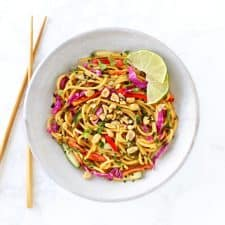 Thai noodle salad with peanut dressing with chopsticks in grey bowl.