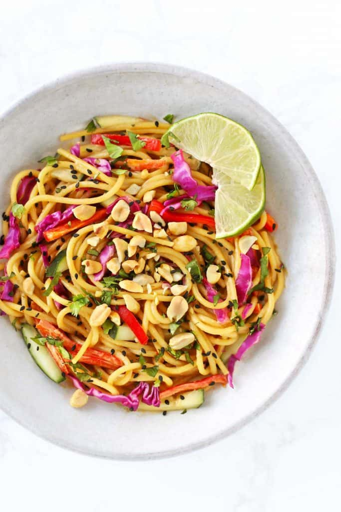 Thai noodle salad with peanut dressing in grey bowl with limes.