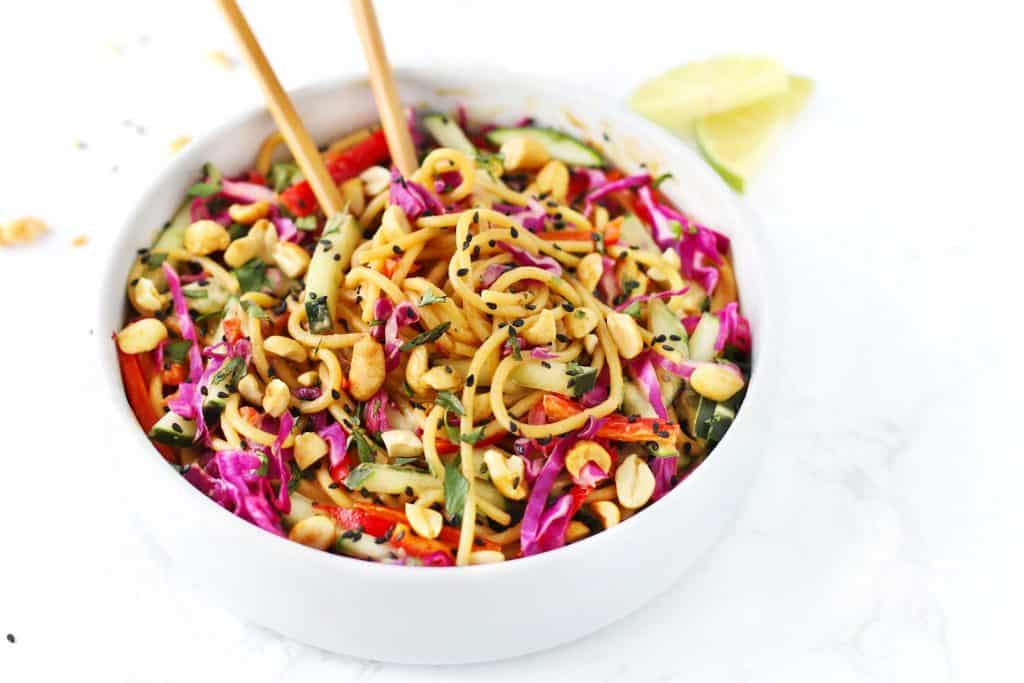 Thai noodle salad with peanut sauce in white bowl with chopsticks.