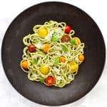 Creamy basil cashew pasta with tomatoes in black bowl.
