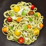 Pasta with green sauce and tomatoes in dark grey bowl.