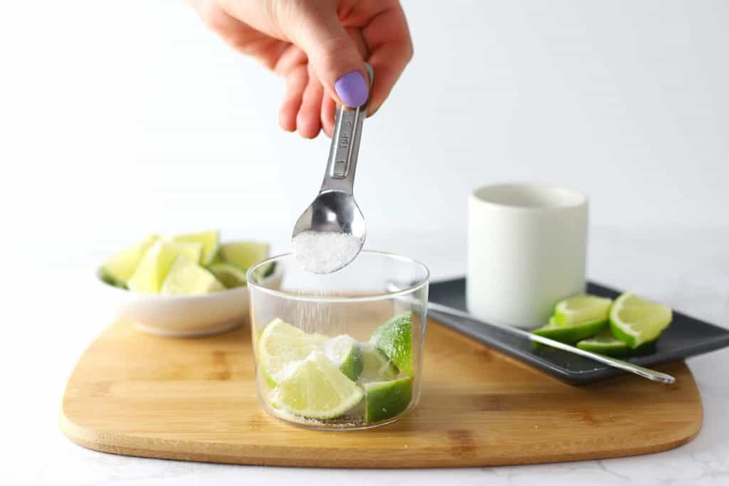 Pouring sugar over limes in a glass.