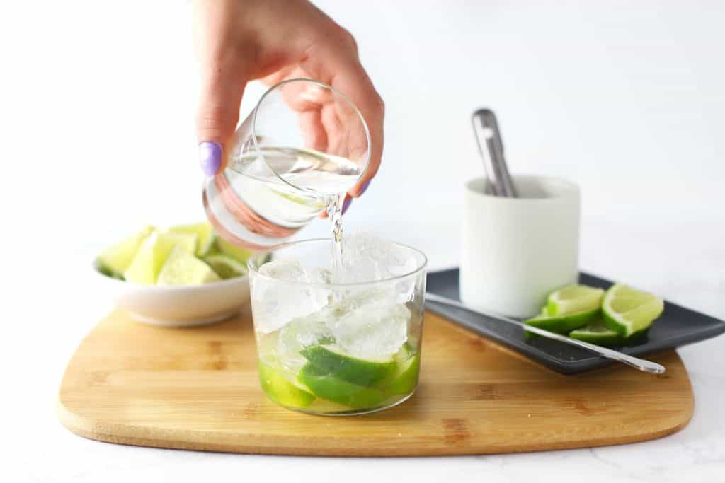 Pouring cachaca into a glass.