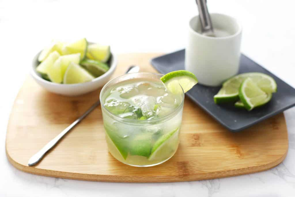 Caipirinha in glass on cutting board with limes and sugar.