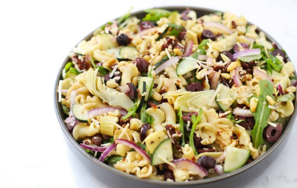 Mediterranean pasta salad in grey bowl.