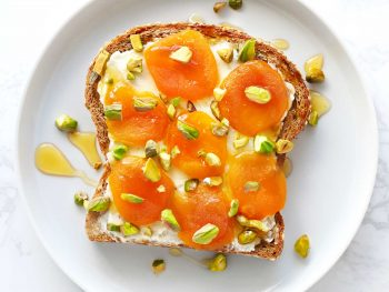 Dried apricot and mascarpone toast on white plate.