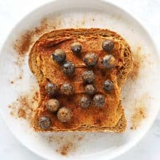 Peanut butter blueberry toast on white plate with cinnamon.