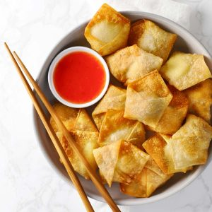 Cream cheese wontons on white plate.