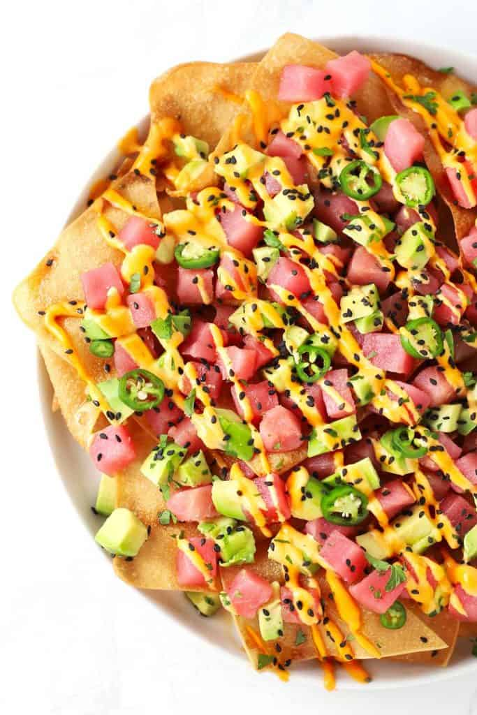 Spicy ahi tuna wonton nachos on white plate.