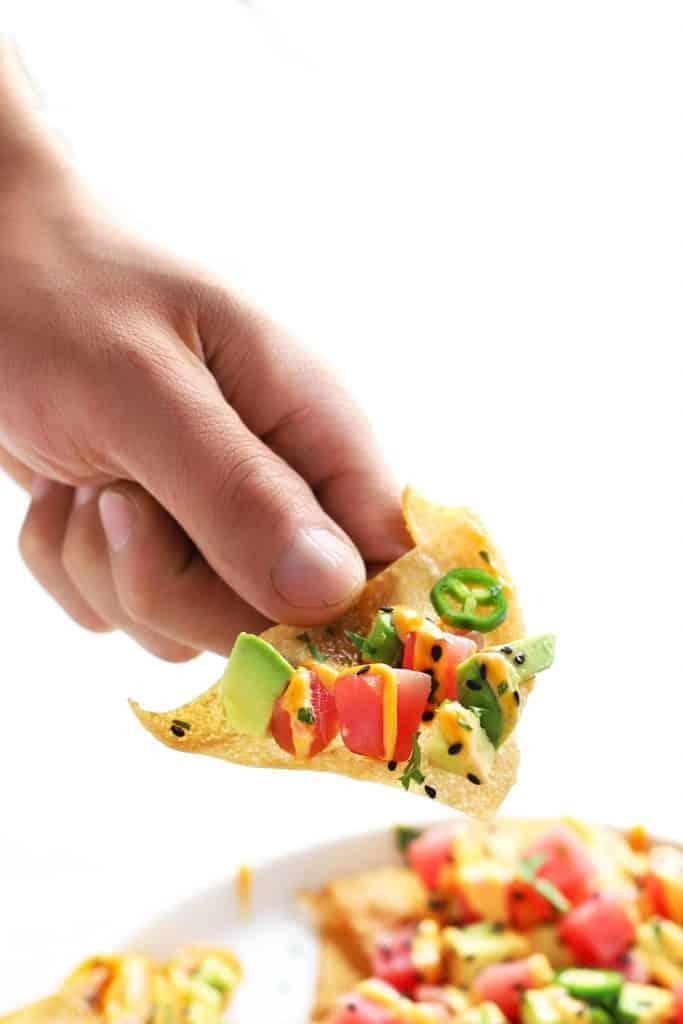 Hand holding a spicy ahi tuna wonton nacho.