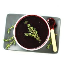 Blueberry lemon thyme sauce in white bowl with wood spoon.
