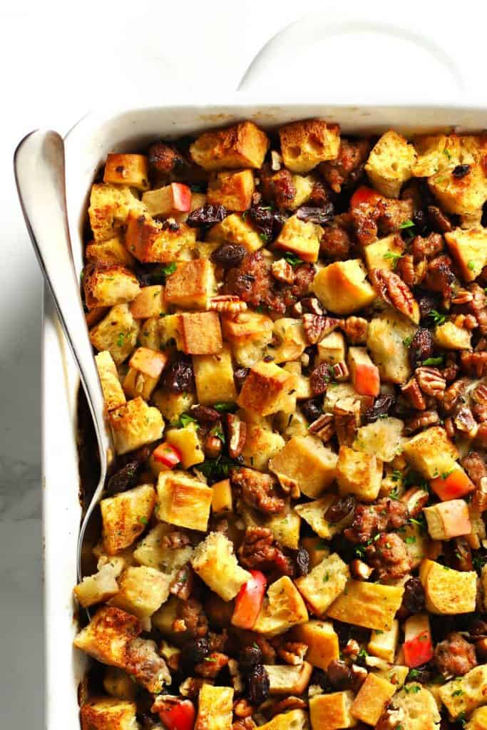 Italian sausage apple stuffing in white baking dish.