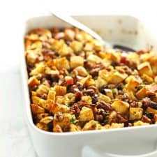 Stuffing in white casserole dish with serving spoon.