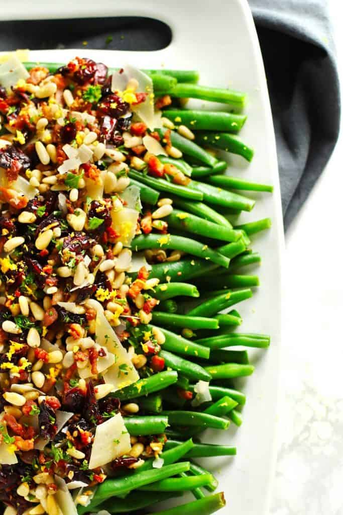 Lemon garlic green beans with crispy pancetta on white tray.