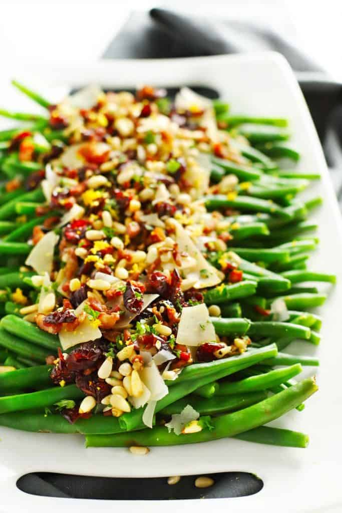 Lemon garlic green beans loaded with toppings on white tray.