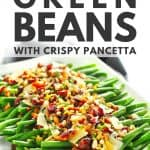 Lemon garlic green beans with crispy pancetta and loaded toppings on white tray.