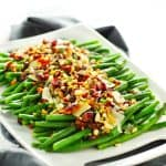 Lemon garlic green beans with crispy pancetta and loaded toppings on white tray with gray napkin.