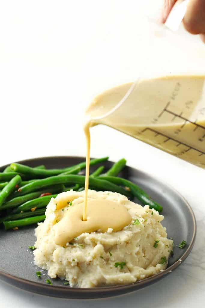 Pouring gravy on mashed potatoes.