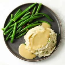 Mashed potatoes and gravy with green beans on grey plate.