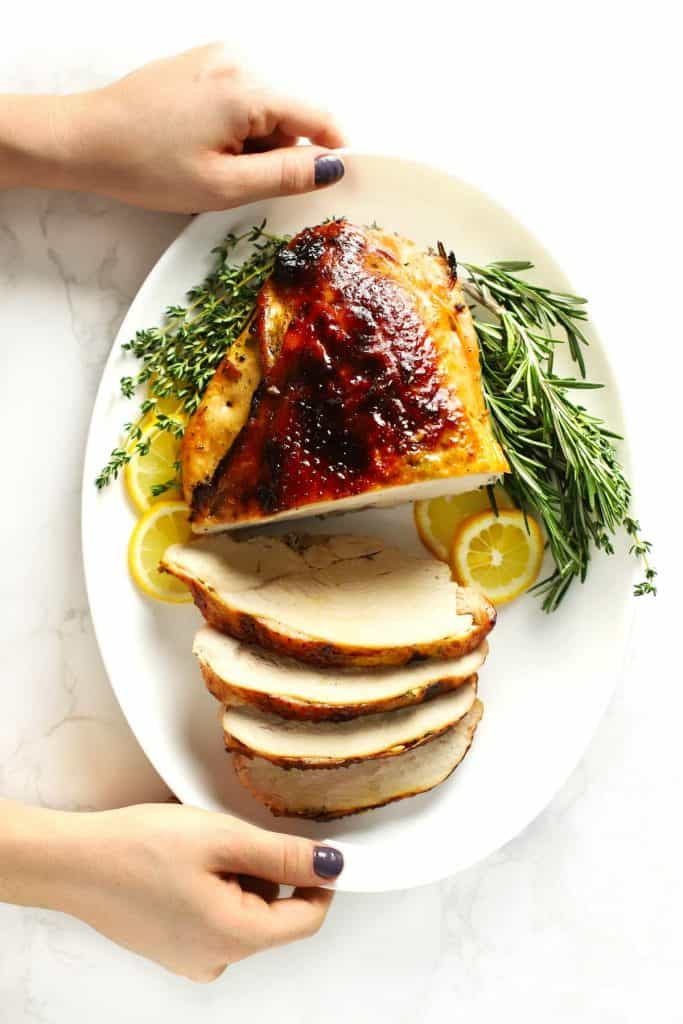 Two hands holding white platter with sliced roasted boneless turkey breast.