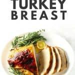 Roasted boneless turkey breast on white platter with fresh herbs.