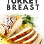 Roasted boneless turkey breast on white platter with fresh herbs and lemons.