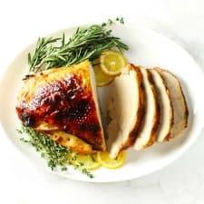 Roasted boneless turkey breast on white platter.