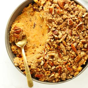 Sweet potato casserole in grey bowl with brass spoon.