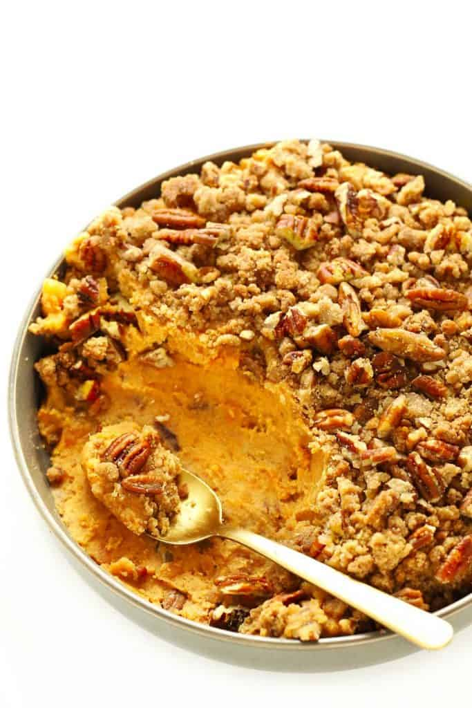 slow cooker sweet potato casserole in grey bowl with gold spoon.